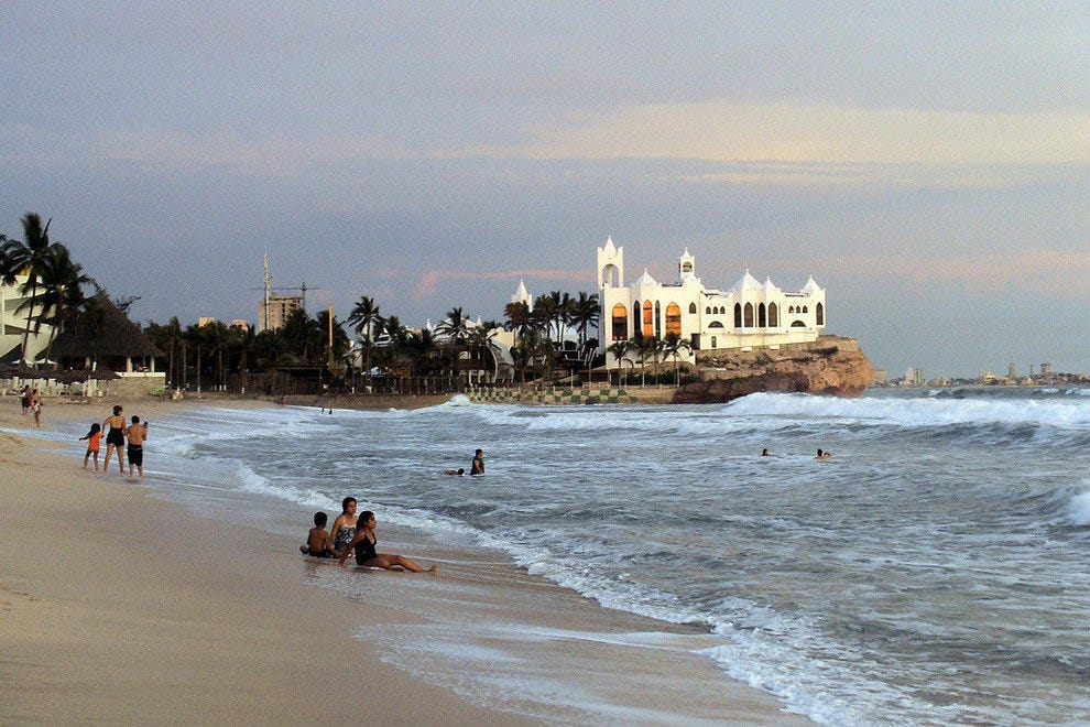Swimmers and sunbathers enjoy the sand and surf at Mazatlan