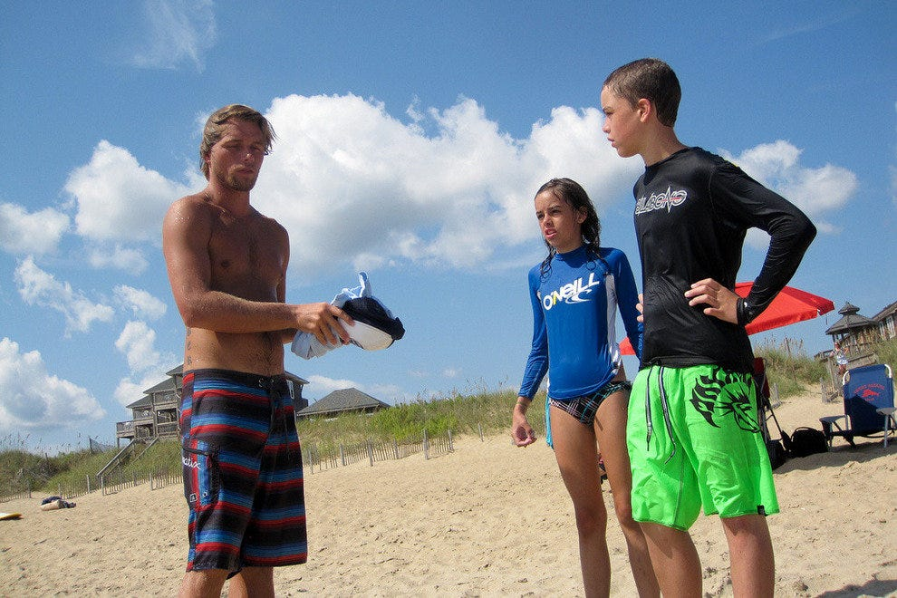 Surfing instructor with two students on an Outer Banks beach