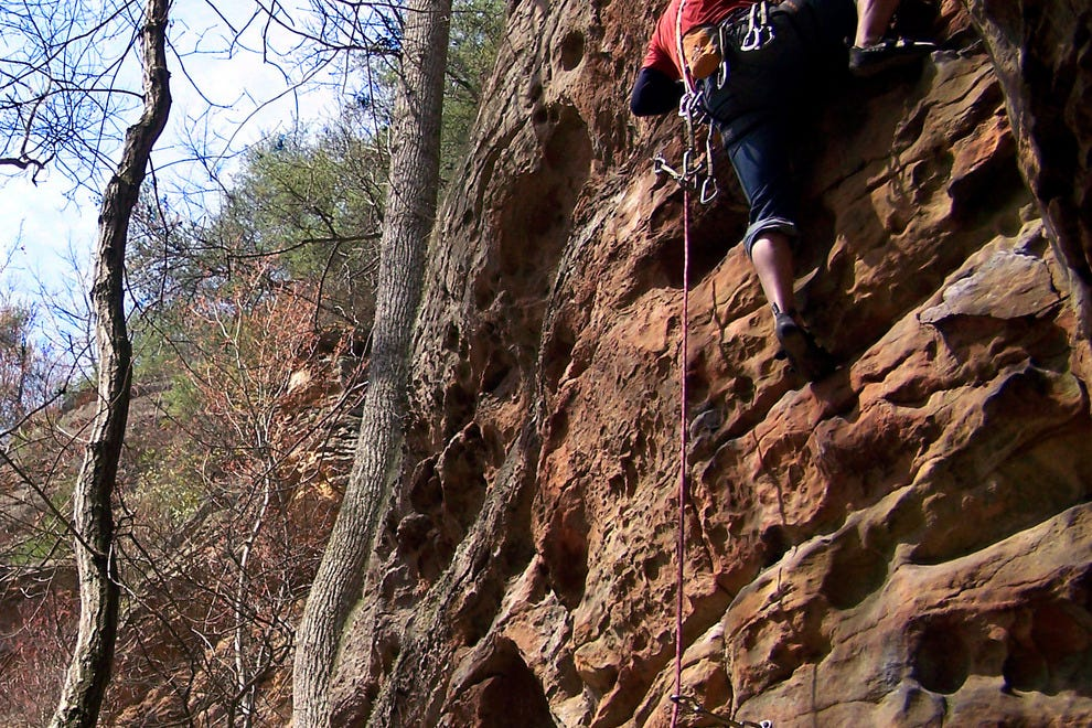 A rock climber makes his way to the top.