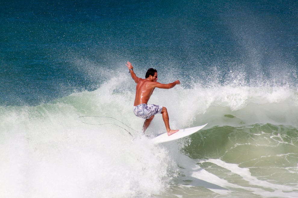 Riding a wave off Leme Beach
