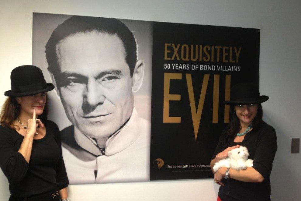 "Two would-be James Bond villains stand in front of a poster advertising the new ""Exquisitely Evil"" exhibit"