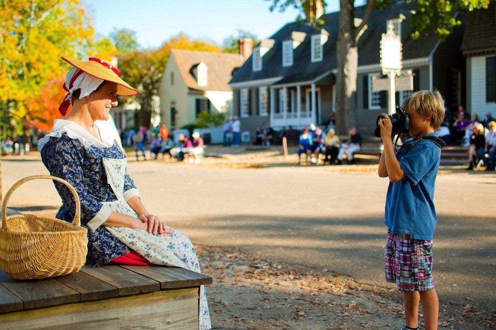 A boy photographing a Colonial Williamsburg resident