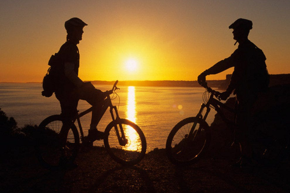 A pair of mountain bikers pause to admire an Atlantic Ocean sunset.