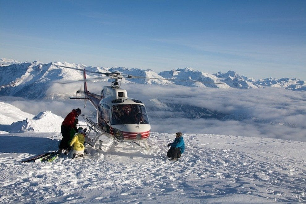 Skiers unload gear from a helicopter in the backcountry near Whistler.