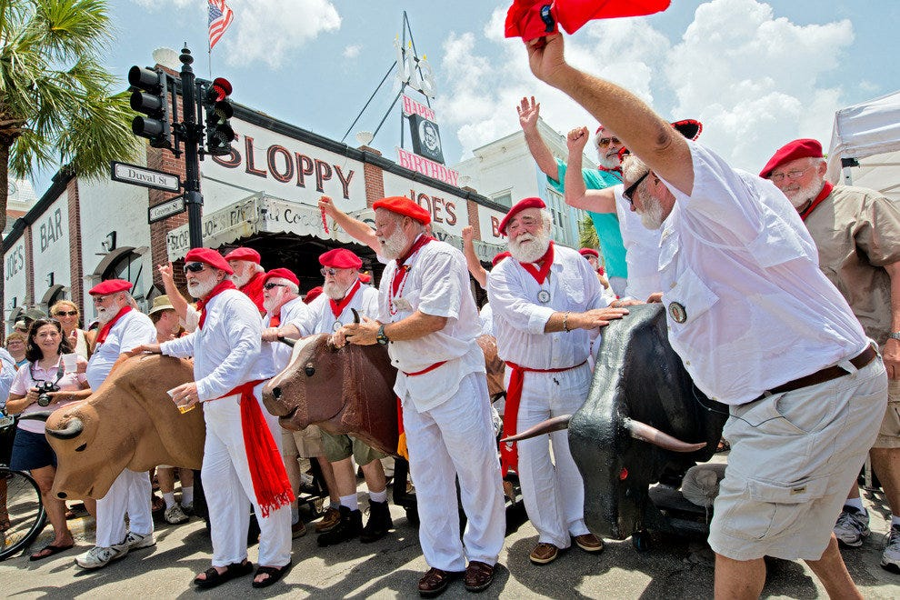 "Ernest Hemingway look-alikes push fake bulls on Duval Street during the ""Running of the Bulls."""