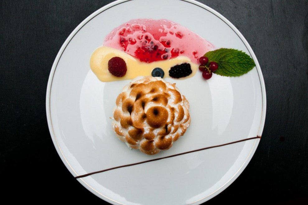 Baked Alaska with fresh berries, berry coulis and caramel sauce.