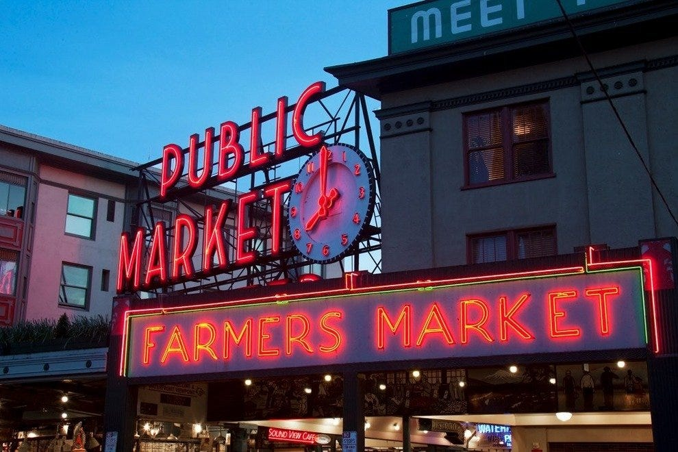 The iconic Pike Place sign illuminates downtown Seattle