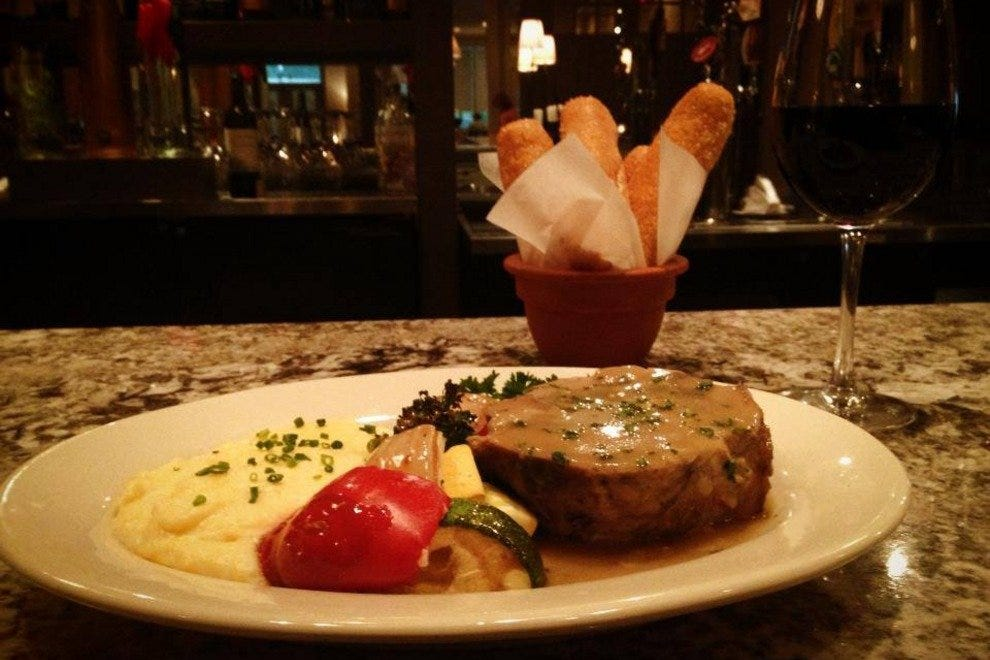 Fiore's entrees, like the porchetta with roasted vegetables and polenta, come with the eatery's signature breadsticks