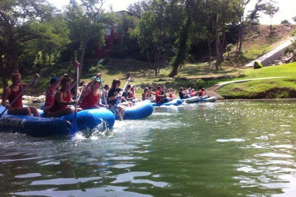 Teams paddle down the Guadalupe River with Rockin' R River Rides