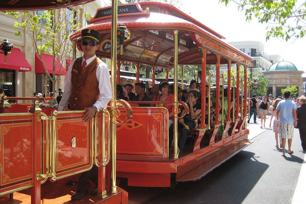 A trolley takes guests around The Americana at Brand.