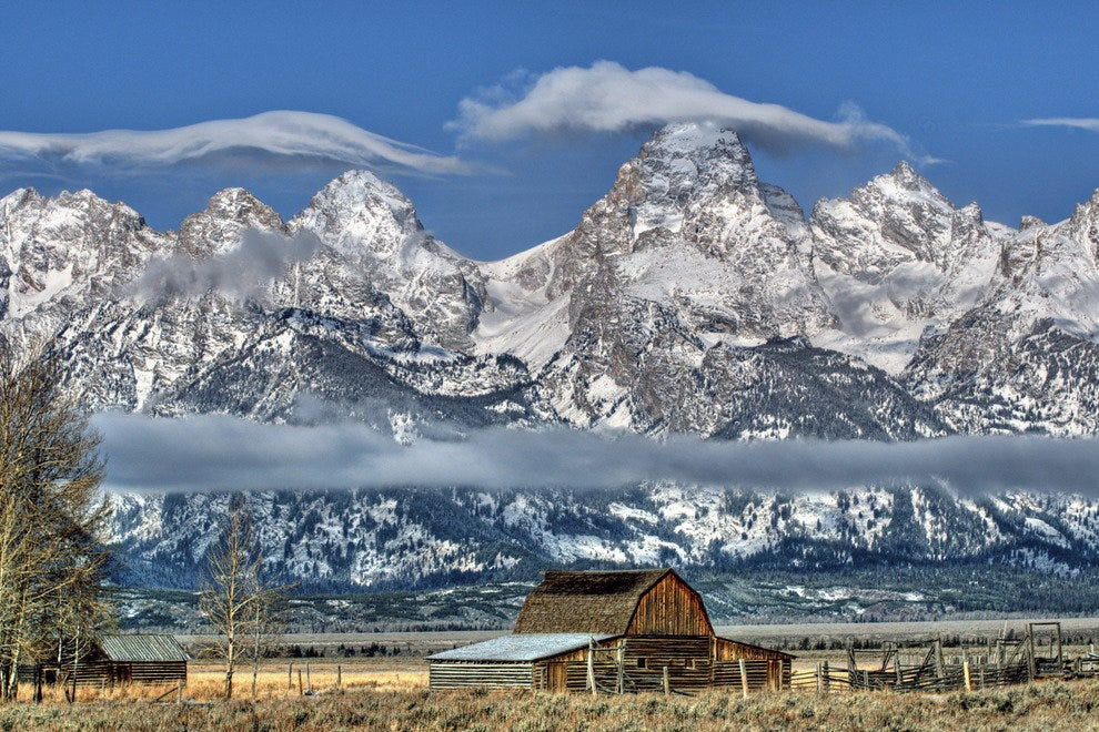 The Tetons tower behind a homestead on Mormon Row in Wyoming
