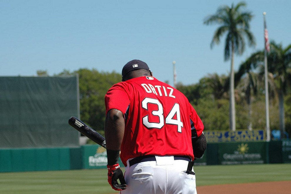 Big Papi taking some batting practice cuts with palm trees in the background