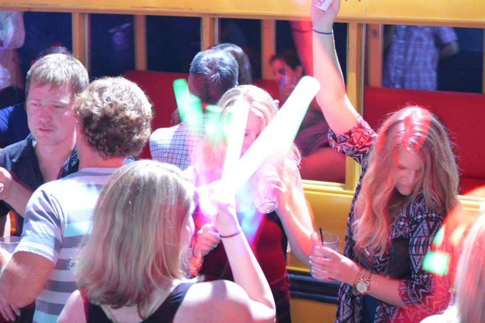 Club patrons dance in front of The Pawn Shop's VIP bus.