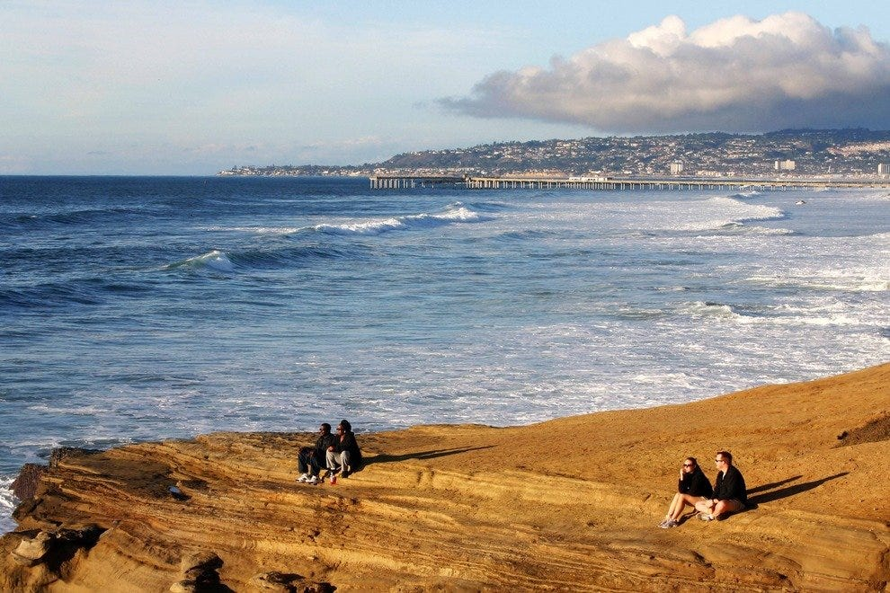 Couples enjoy the beauty of Sunset Cliffs.