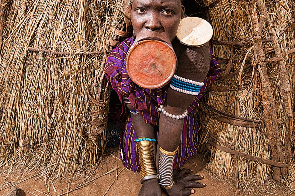 Mursi woman in front of her hut
