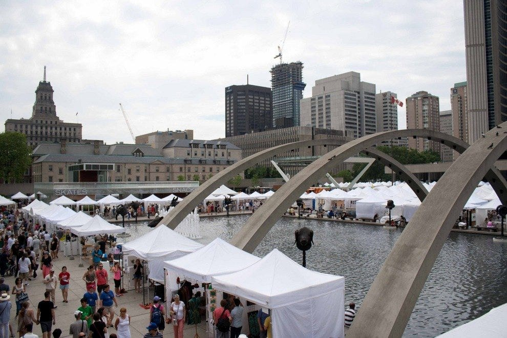 The freedom arches of Nathan Phillips Square work as an outdoor frame for this art event