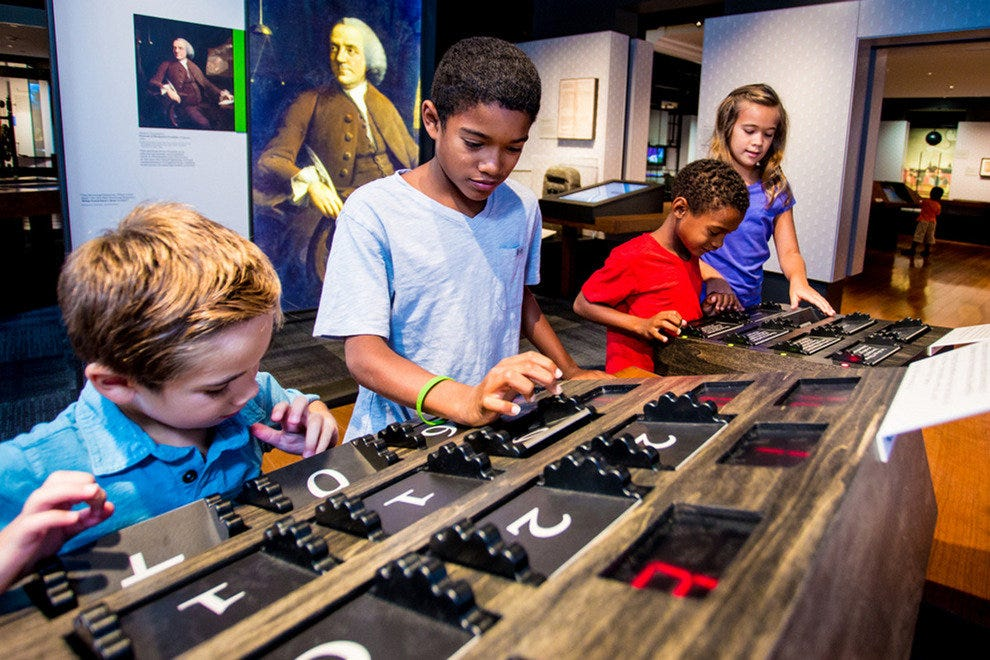 Children learn about Benjamin Franklin through interactive displays at the museum
