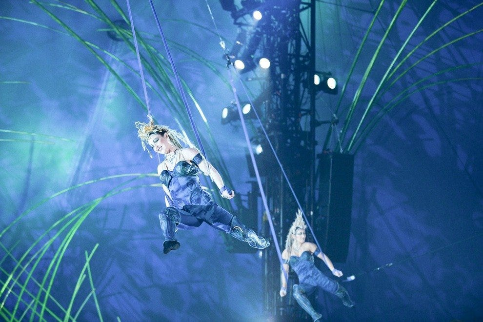 Cirque du Soleil performers fly above on aerial straps