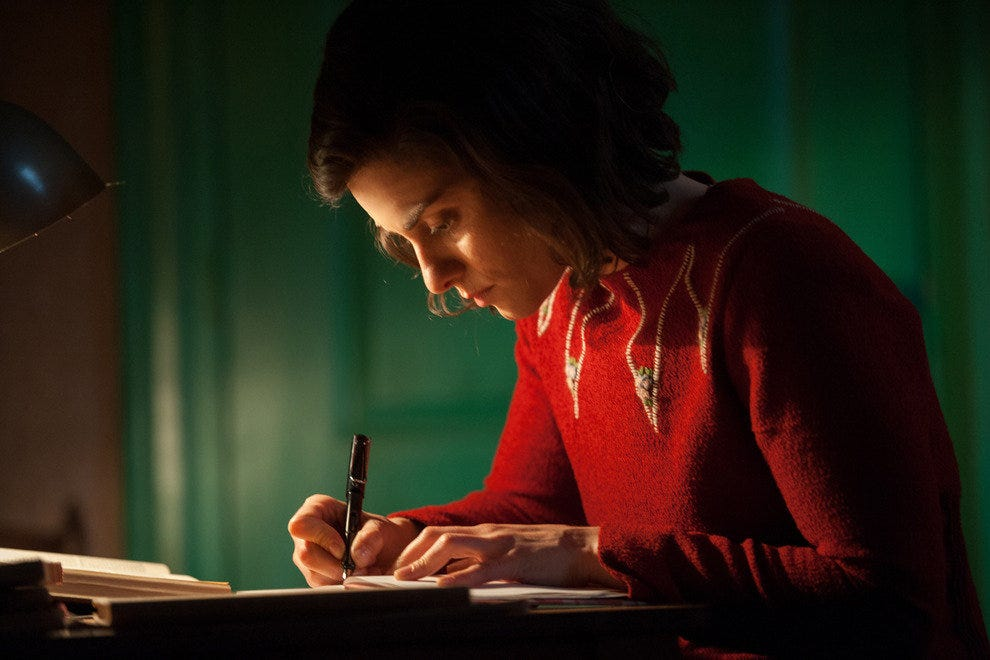 Anne Frank, played by actress Rosa da Silva, writes in her diary