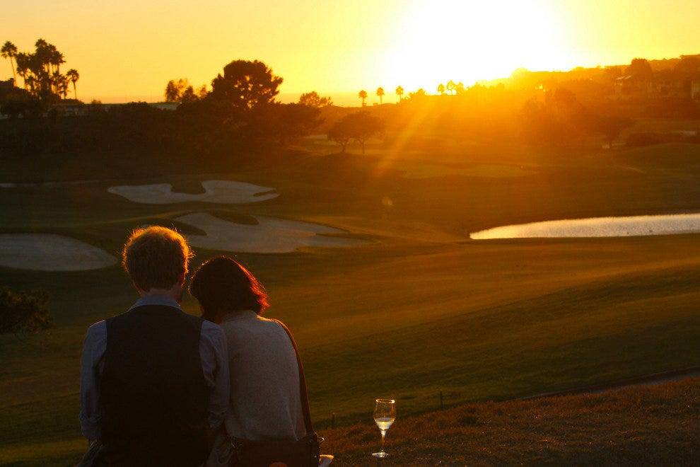 A couple enjoys the sunset over the Monarch Beach Golf Links.