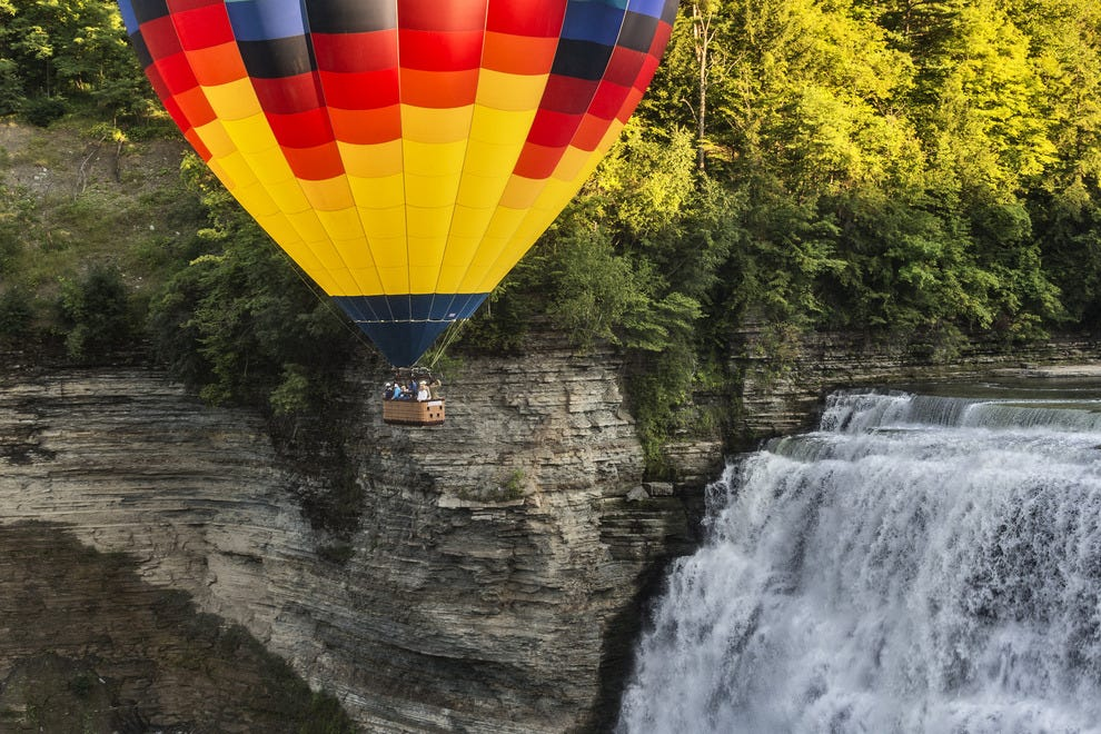 A hot air balloon floats near one of the cascading waterfalls in Letchworth State Park