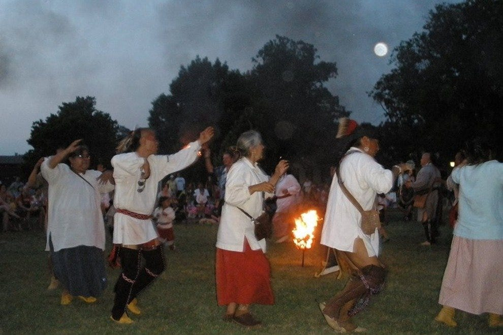 Warriors and friends enjoy the Bear Dance during an evening program with fire and a full moon