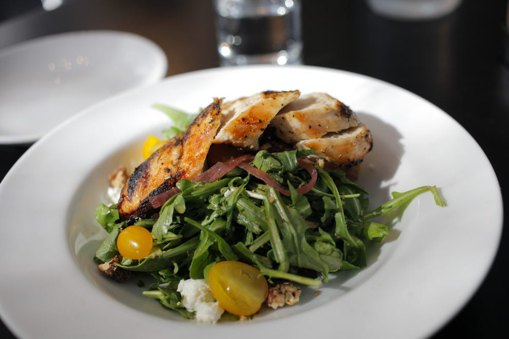 Lighter fare like the baby arugula salad topped with grilled chicken are also available in half portions, as seen here