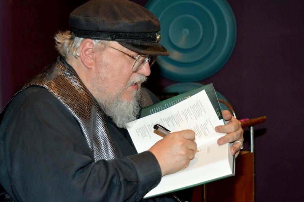 George R. R. Martin, autographing one of his books
