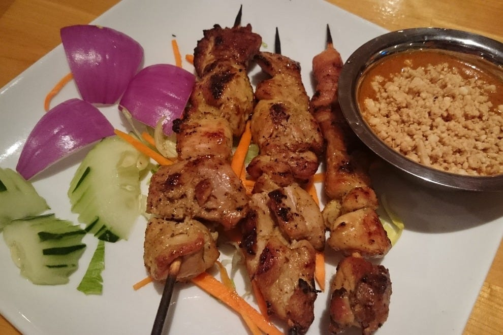 Chicken satay is served with an ample side of peanut sauce