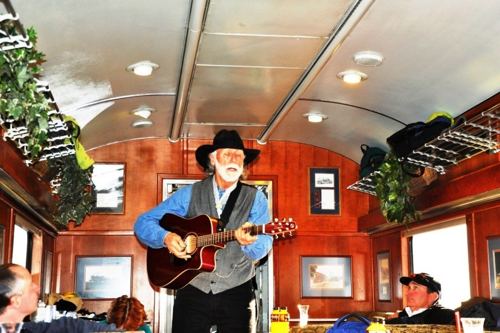 The strolling cowboy musician entertains the passengers car by car