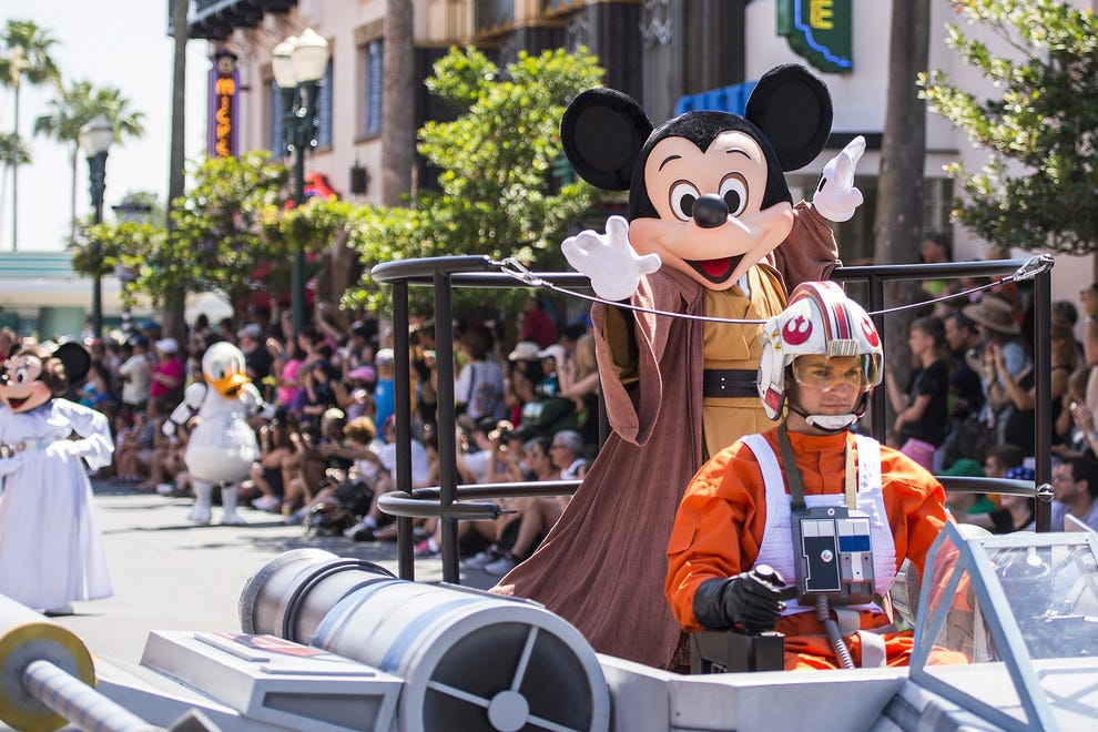 Mickey, donning his finest Jedi robes, enjoys the ride at the Legends of the Force motorcade