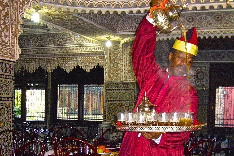 An adept Berber waiter pours mint tea, the favored Moroccan drink either hot or iced.