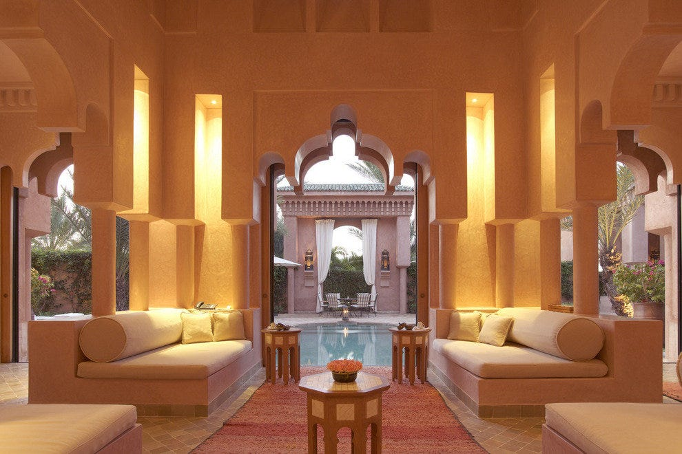 This guest room in luxury Amanjeena Resort in Marrakech is graced with keyhole doors looking out on a pool.