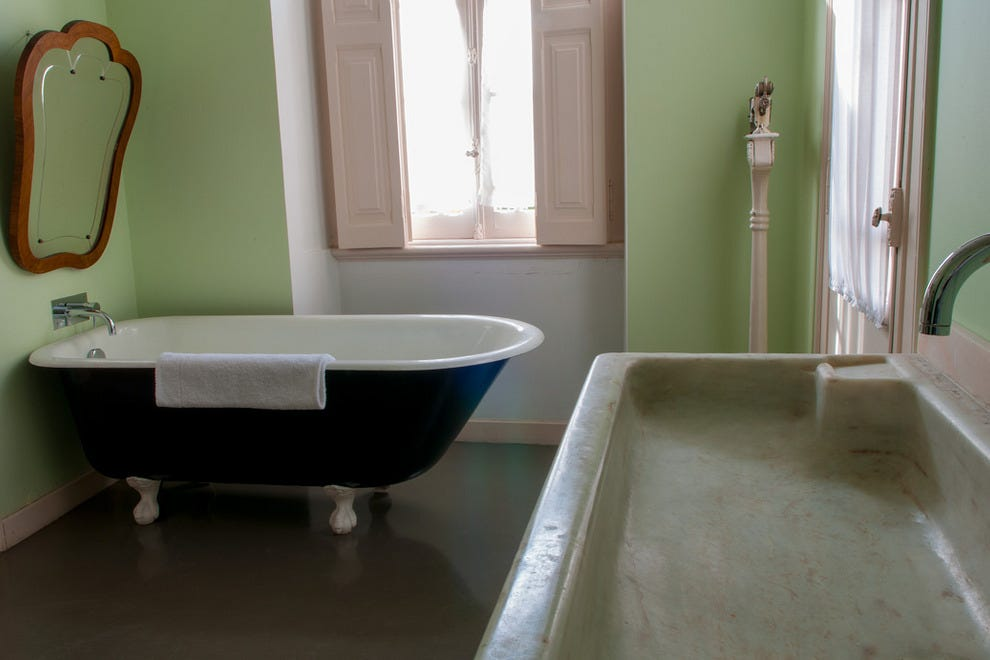 Guest suites feature en-suite bathrooms furnished with period artifacts, such as marble sinks and enamel bathtubs