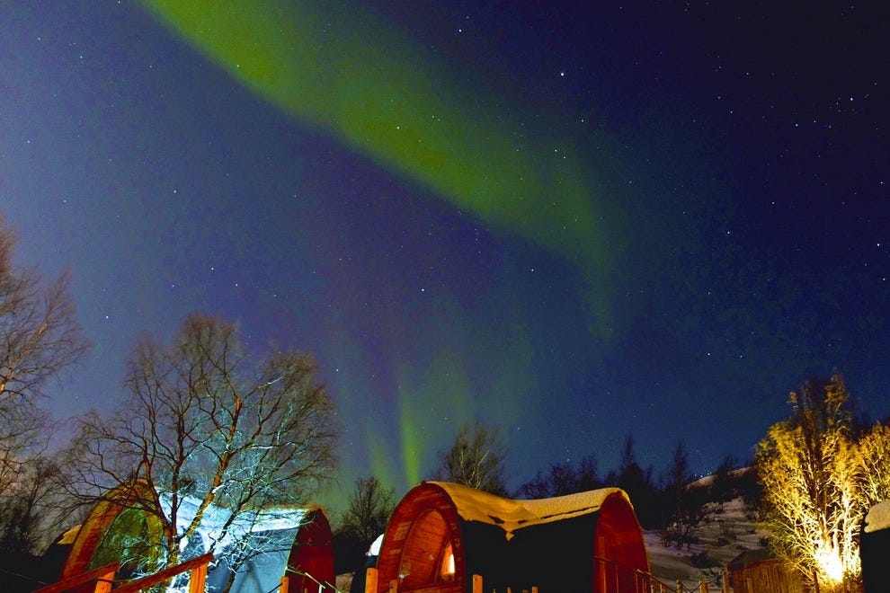 Northern Lights dance over cabins at Snowhotel in Kirkenes, Norway