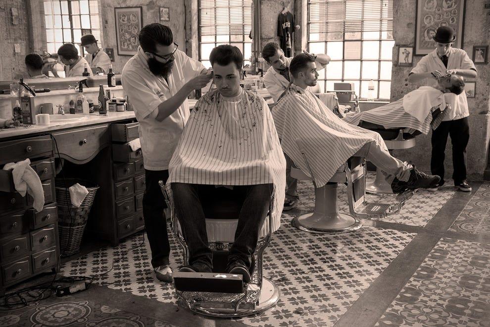 顾客坐在菲加罗理发店工作人员提供的原始Koken理发椅上,在里斯本市中心