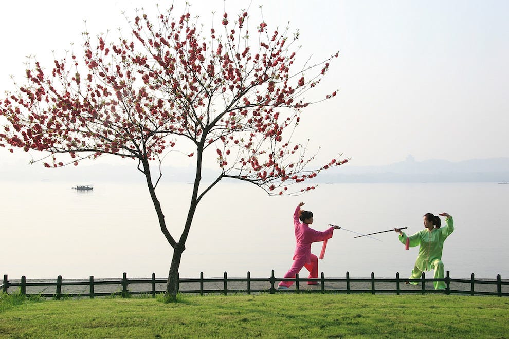 Two people practice Chinese swordplay next to West Lake