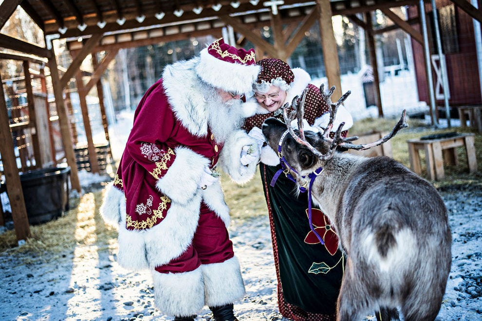 Look like the real Santa and Mrs. Claus visiting the reindeer at Santa Claus House in North Pole, Alaska