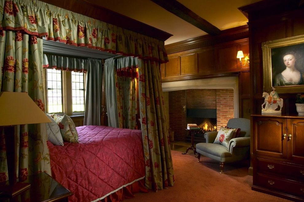 This curtained and canopied bedroom is one of 15 at Buckland Manor