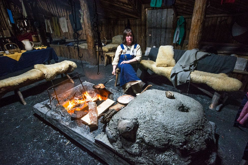 A costumed interpreter cooks over an open flame at the L'Anse aux Meadows Norse site