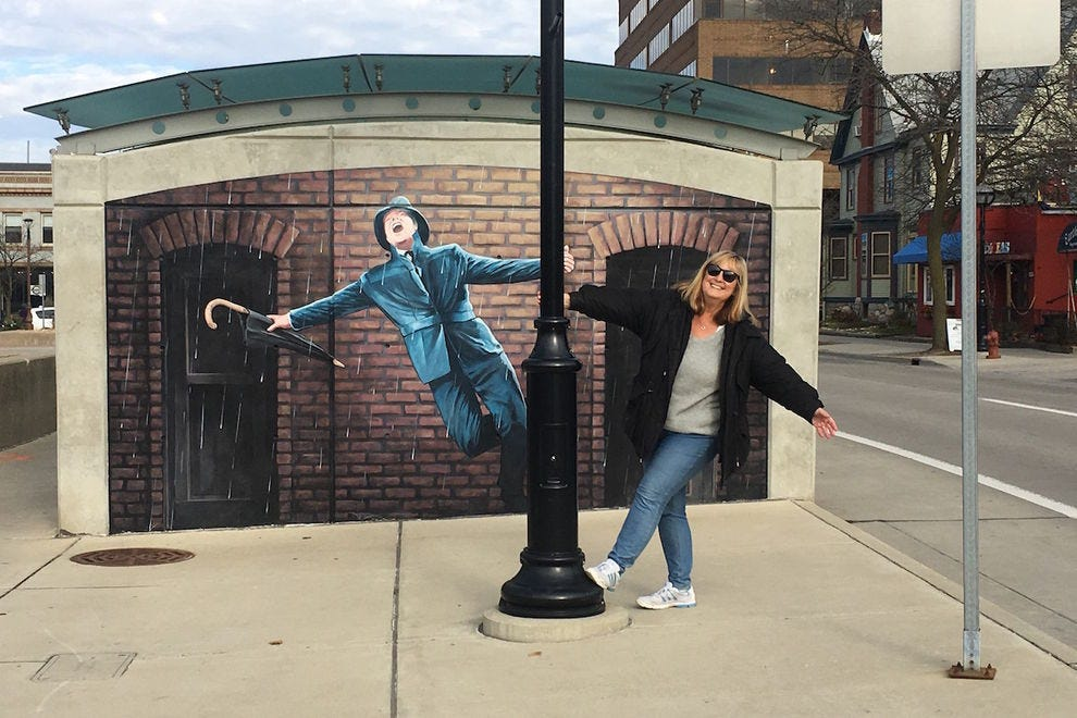 "Pose with Gene Kelly by David Zinn's ""Laughing at Clouds"" mural"