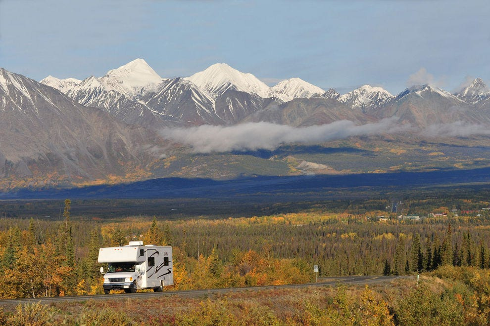 A lone RV cruises near Haines Junction, with the front range of St. Elias Mountains towering in the background
