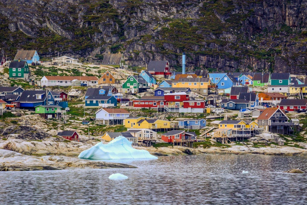 An iceberg floats in front of the town of Ilulissat in Western Greenland