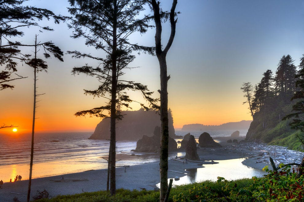 Sun sets behind the Pacific Ocean at Ruby Beach
