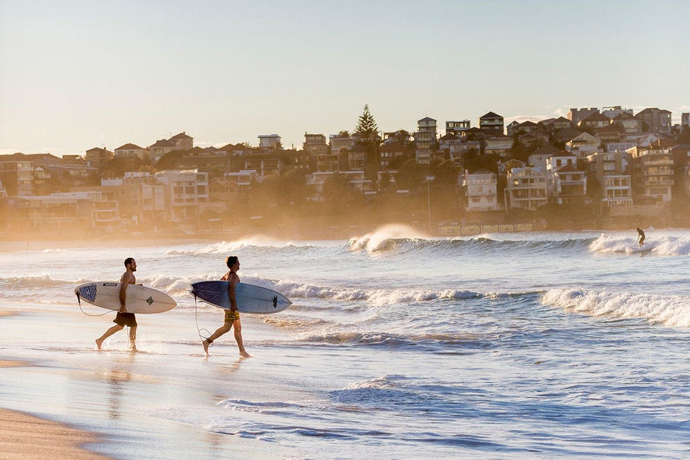 Wave chasers head for a morning surf at Bondi Beach, one of the city's most popular destinations