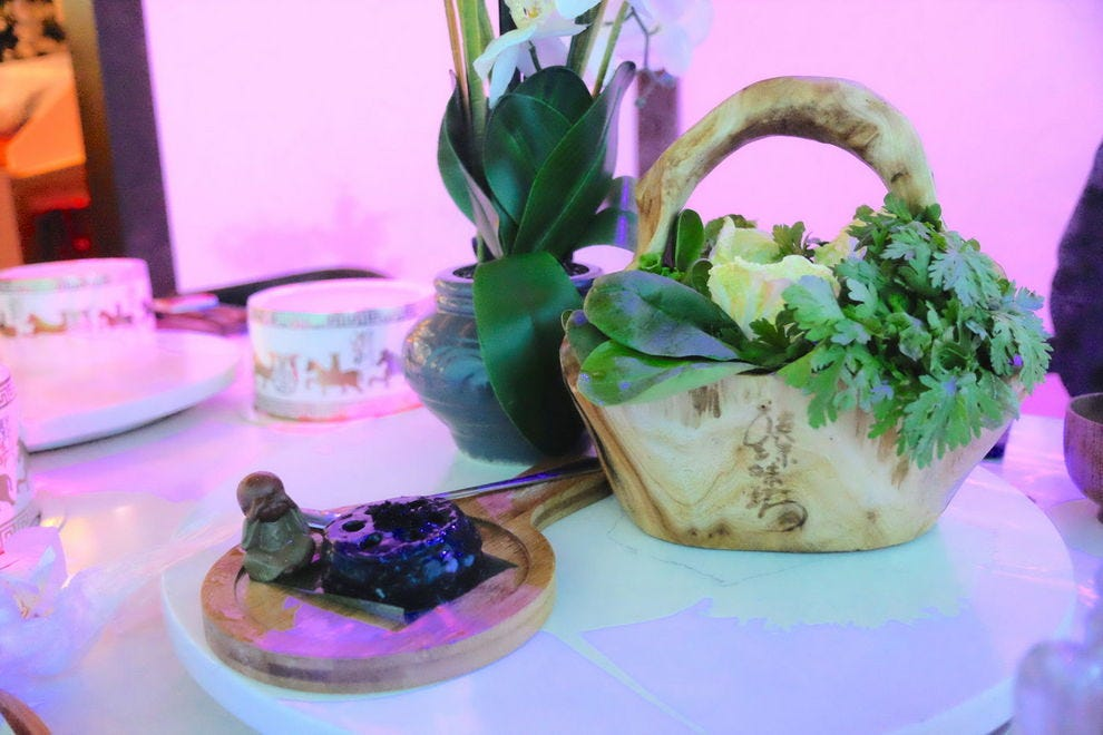 Black cuttlefish paste and a wooden basket of greens