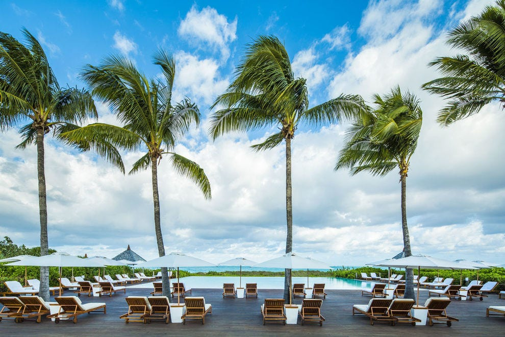 The resort's main swimming pool blends into the Caribbean horizon; surrounded by Lotus restaurant and the beach bar