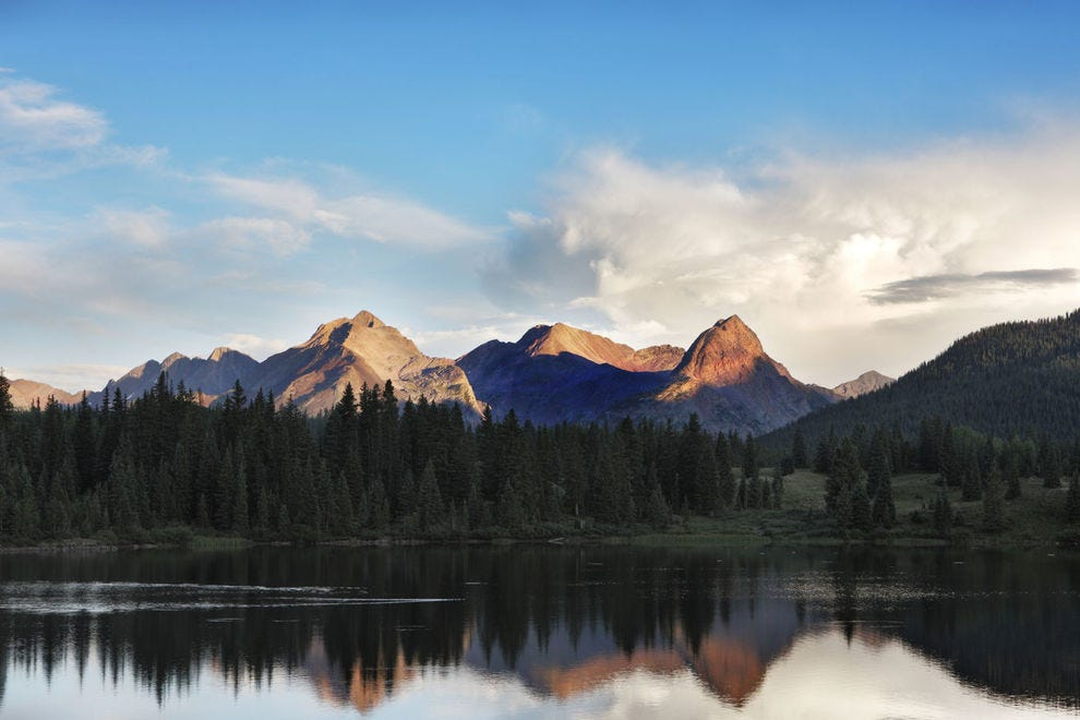 San Juan Mountains and surrounding forest reflect in Molas Lake at dusk