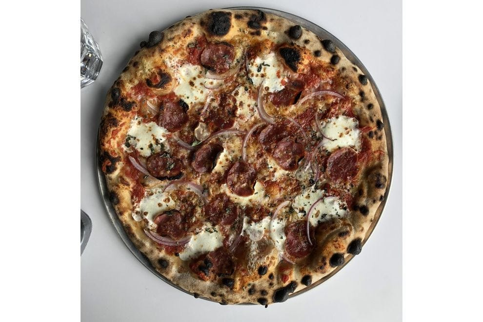 A soppressata pizza with provolone piccante, red onion and preserved hot peppers.