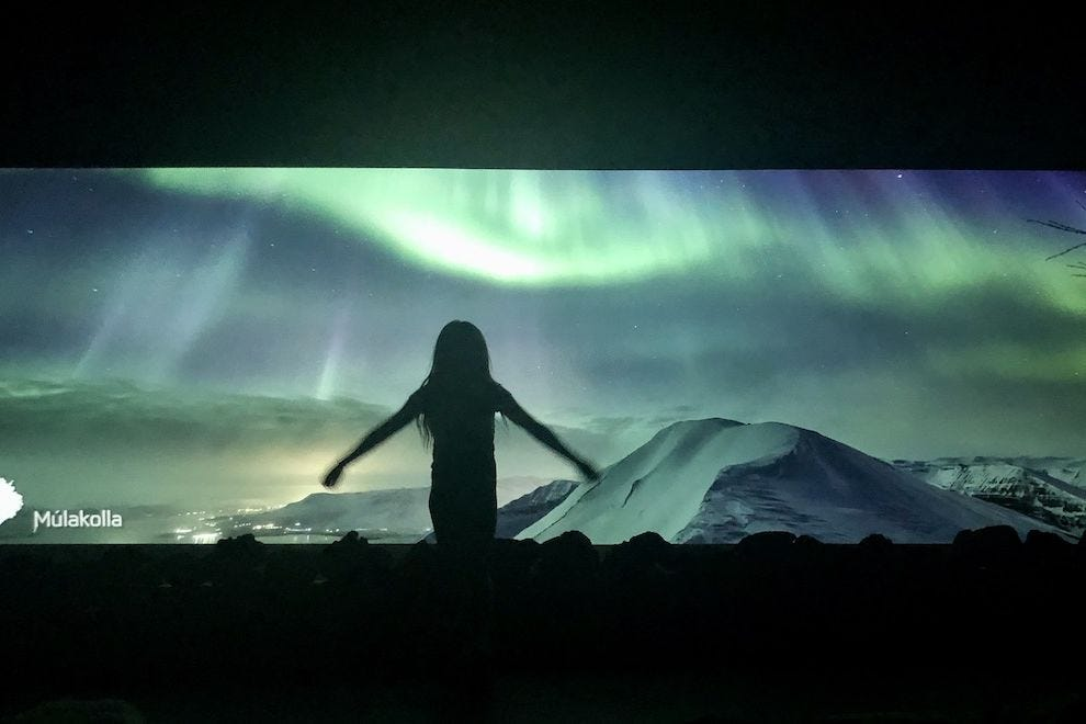 A woman standing in front of the photo projection at the Northern Lights Center